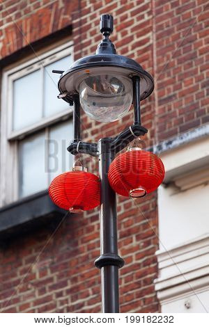 Red lanterns in Chinese quarter Chinatown London United Kingdom. Chinatown contains a number of Chinese restaurants bakeries supermarkets souvenir shops and other Chinese-run businesses.