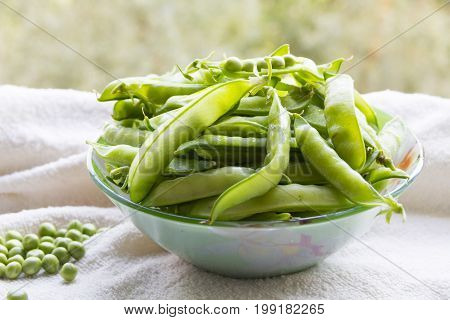 Green peas. Pile of peas and peas in bowls on the table