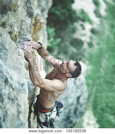 adult man rock climber. rock climber climbs on a rocky wall. man hold the cliff the both hands. focus on the fingers