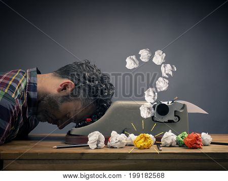 Businessman gets an idea while dreaming or sleeping creativity concept with crumpled paper with an old typewriter on a wooden office desk