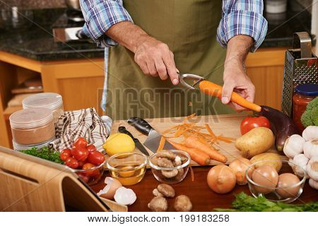 Hands of male cook using peeler when preparing carrot for the dish
