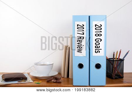 2017 review and 2018 goals. Two binders on desk in the office. Business background.