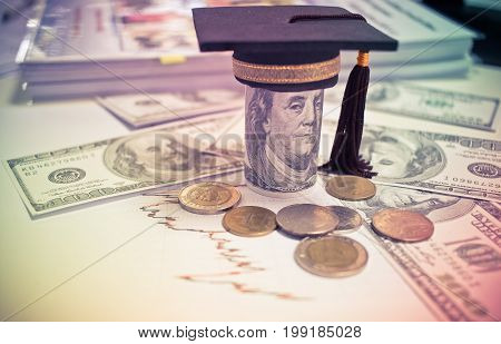 Concept of international graduate study graduation black cap on pile of foreign money US dollars Asian Thai coins Education certificate of Abroad program. Vintage stlye