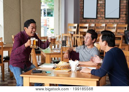 Happy man bringing beer mugs to the table where his friends are sitting