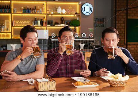 Group of Vietnamese mature men enjoying tasty fresh beer in the bar