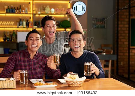 Mature Vietnamese men drinking beer and supporting favorite team in sports bar
