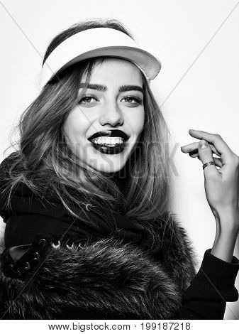 fashion model or happy woman with long hair in sport cap and fur black and white