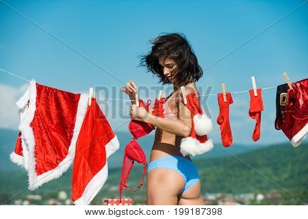 Xmas red costume on rope with pin. Santa claus girl hanging clothes for drying. Christmas woman with buttocks outdoor. Laundry and dry cleaning. New year girl on sunny blue sky.