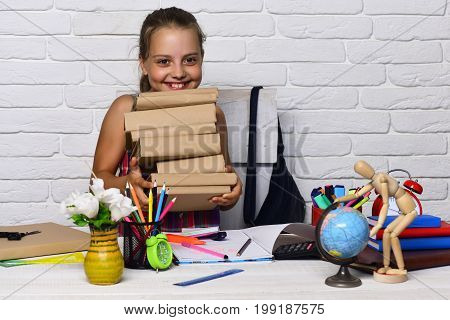 Schoolgirl With Happy Face Holds Big Pile Of Books