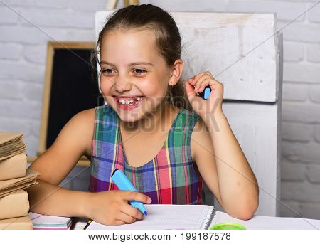 Girl Sits At Desk With Books And Stationery