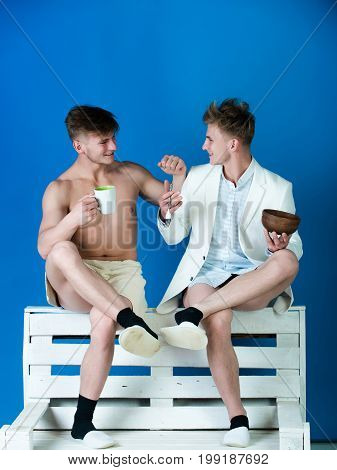 Men smiling on wooden bench on blue background. Drinking and healthy dieting. Businessman wearing shirt jacket and underpants. Macho with muscular torso wrapped in towel. Fashion and fitness concept.