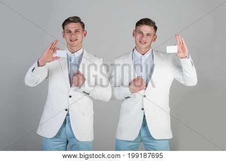Business communication and meeting. Cooperation and partnership. Banking and saving concept. Happy men holding blank cards on grey background. Businessmen wearing white jackets.