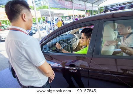 Dongguan, Guangdong, China - August 7, 2017: Car salesperson talking with prospective Chinese brand automobile buyer at Dongguan car exhibition