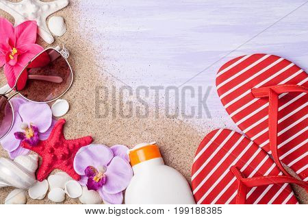 Summer holiday background. Beach accessories sunglasses shoes flipflop sunscreen and seashells on blue surface top view. Vacation and travel concept. Copy space