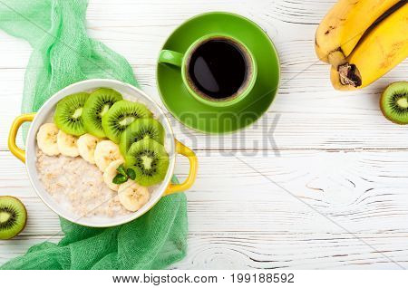 Breakfast with oatmeal porridge coffee cup and fruits. Oatmeal with kiwi and banana. Healthy breakfast and eating concept. Top view. Copy space