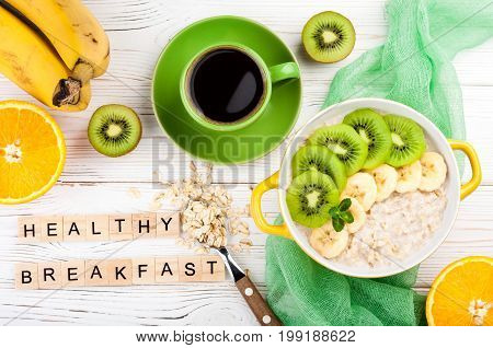 Breakfast with oatmeal porridge coffee cup and fruits. Oatmeal with kiwi and banana. Healthy breakfast and eating concept. Top view