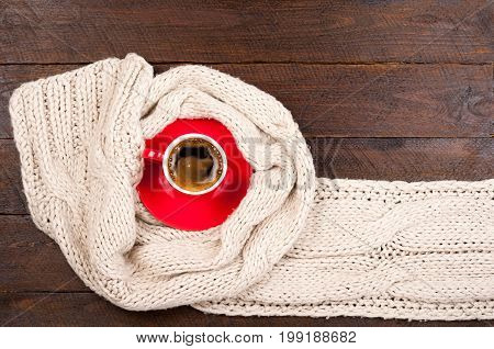 Woolen scarf and coffee cup on wooden table. Wintr background. Hot coffee break concept