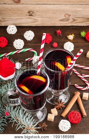 Mulled wine in glass with spices and citrus fruit. Christmas background