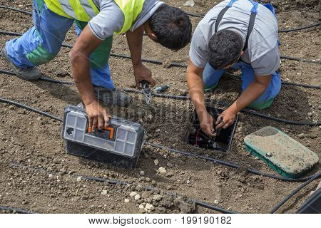 Garden Workers Installing Irrigation Control Box
