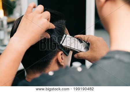 Hairstylist trimming hair on temples of male client