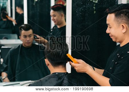 Professional Vietnamese hairstylist finishing his work on haircut for a young man