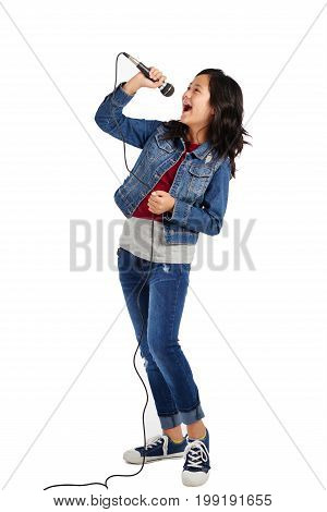 Studio shot of talented mixed-race girl singing in microphone