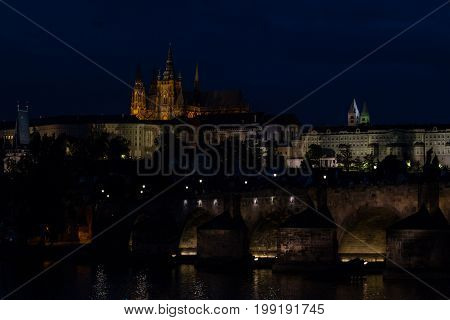 Nightly view of old town with St. Vitus Cathedral and Charles Bridge in Prague.