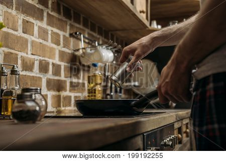 Partial View Of Man Preparing Eggs For Breakfast In Kitchen At Home