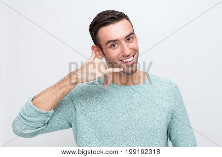 Closeup portrait of smiling young man looking at camera and making call me gesture. Isolated front view on white background.