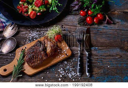 Pork Steak With Vegetables And Herbs On A Rustic Wooden Board Over Rough Wooden Desk With A Copy Spa