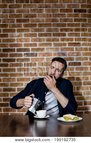 Handsome Bearded Young Man Drinking Coffee And Yawning And Eating Sandwich At Morning