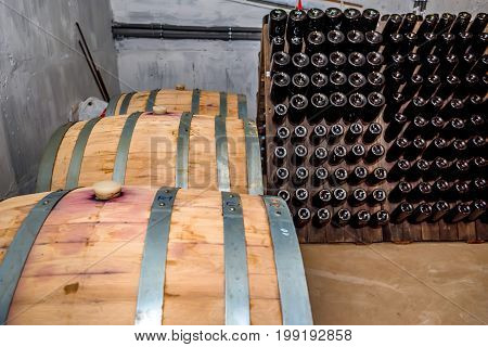 Close up wine barrels in cellar with wine bottles on stand in background