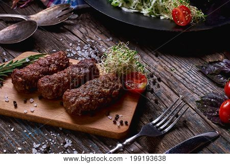 Products Grill: Steak, Sausage And Vegetable On A Rustic Wooden Table. Sausages On The Grill Pan On