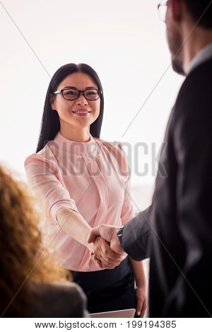 Business woman shaking hands with a partner. Successful deal is finished, partners concluding a deal.
