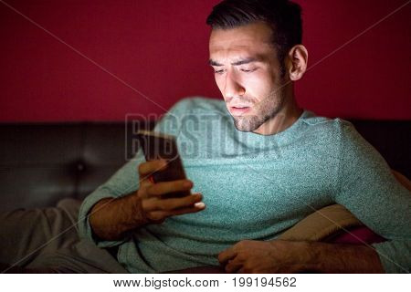 Closeup portrait of worried young handsome man lying on sofa and using smartphone at night at home