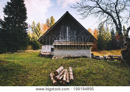 Old house in the autumn forest. Wooden cottage in the valley. Domestic countryside life in Slovenia. Triglav National Park