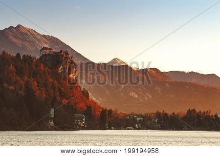 Amazing view on Bled Lake on sunrise. View on Bled Castle and village with Alps on background. December morning on the lake at dawn. Autumn Winter in Slovenia Europe.