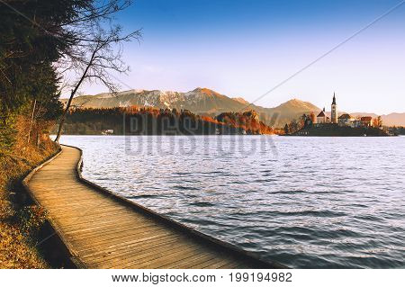 Amazing view on Bled Lake on sunrise with wooden promenade. Island with Catholic Church in Bled Lake with Castle and Mountains. Morning on the lake at dawn. Autumn Winter in Slovenia Europe.