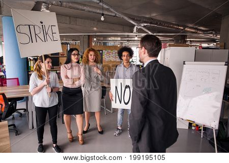Loft style modern office, employees striking. Director negotiating with striking business team.