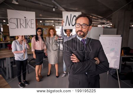 Unsatisfied employees on strike in the office, director standing with his back to employees. Modern office concept.