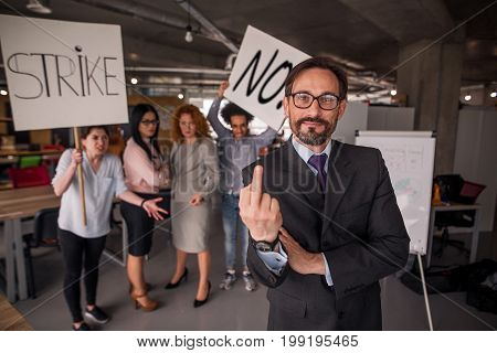 Director showing long finger, employees holding posters with words strike and no. Strike in the office.