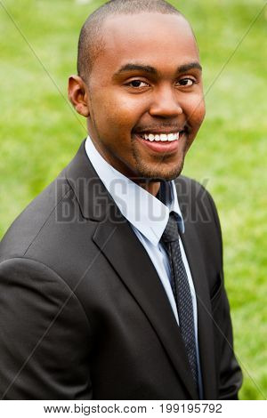 Well dressed young African American man smiling outside.