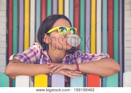 Portrait of beautiful fashionable woman leaning on colorful fence and blowing a bubble gum balloon