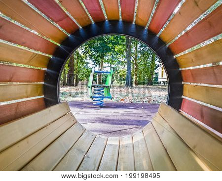 see through empty wood tube at playground for child on green meadow background