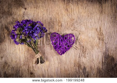 Wicker purple heart and bouquet of dried flowers on an old wooden background.