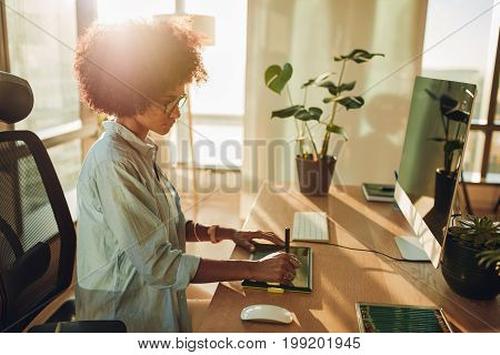 Young hipster graphic designer woman using digital graphic tablet while working at modern office. Professional female retoucher sitting at modern workspace.