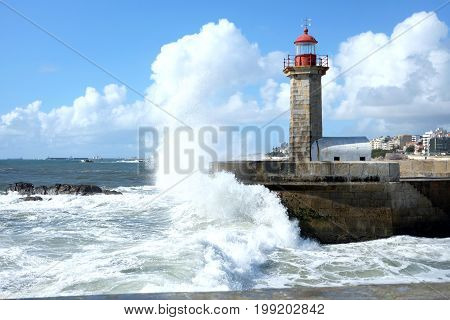 Storm waves over lighthouse and blue sky in Porto Portugal