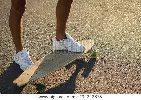 close up picture of legs on white snickers stand on skateboard