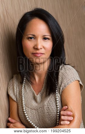 Fashionable beautiful Asian mature woman smiling with copy space.