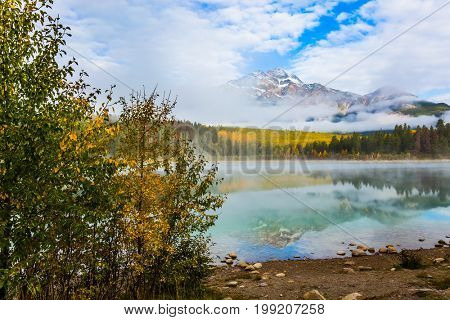 Patricia Lake in the Rocky Mountains. The water reflects the peak of the Pyramid Mountain. Indian Summer in Canada. The concept of ecotourism